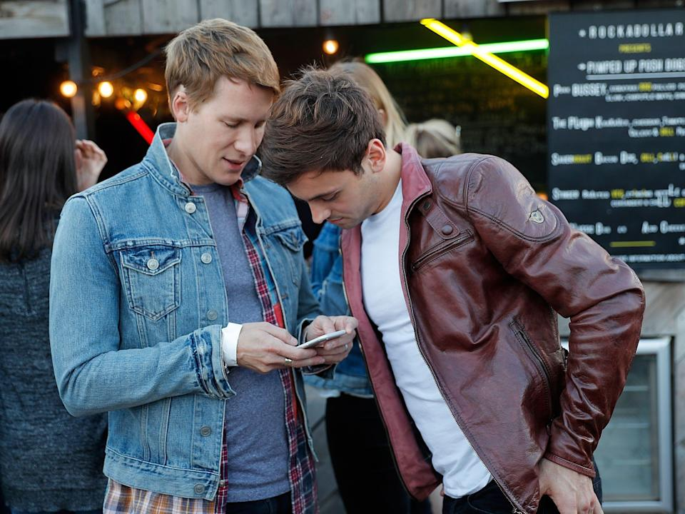 Dustin Lance Black and Tom Daley look at a cell phone