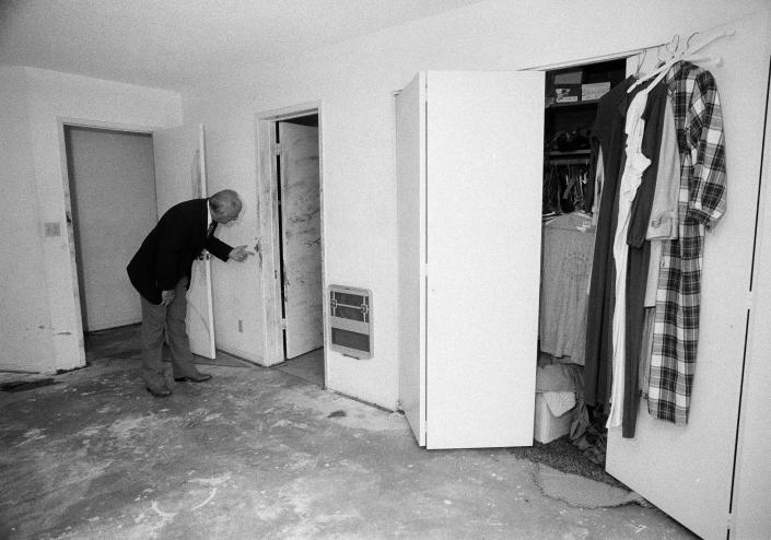 FILE - In this June 8, 1983, file photo, San Bernardino County Sheriff Floyd Tidwell examines blood stains found on the doorway leading into the master bathroom in the home of F. Douglas Ryen and his wife Peggy, in Chino, Calif. The Ryens, who along with their daughter and a neighborhood friend, were found brutally murdered, early morning June 5. The Ryen's son, Joshua, remains hospitalized after being critically injured in the attack. Gov. Gavin Newsom has ordered an independent investigation into the conviction of death row inmate Kevin Cooper, who claims he was framed for the stabbing deaths of four people, including two children, in 1983. Newsom on Friday, May 28, 2021, ordered a law firm to examine all the evidence, including results of DNA testing that Cooper had argued could prove his innocence. Newsom said he's taking no position on Cooper's guilt or innocence. Cooper wants clemency, alleging he was framed for a 1983 knife and hatchet attack on a Chino Hills family that killed four people, including a boy and girl, ages 10 and 11. (AP Photo/Reed Saxon, File)