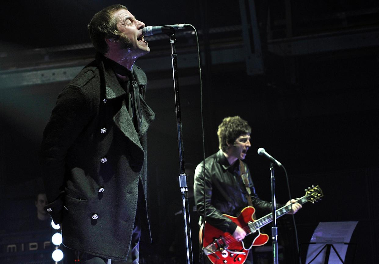 Liam and Noel Gallagher (R) of the band Oasis perform on stage in the southern German city of Munich on February 27, 2009. Oasis are touring around Europe to promote their new