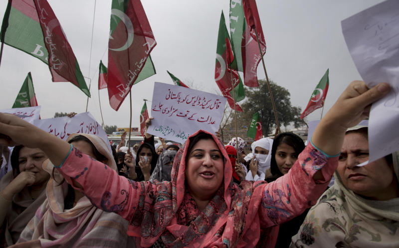 """Women supporters of Pakistan Tehreek-e-Insaf chant slogans during a rally against an American embassy worker Raymond Davis who shot dead two Pakistanis, in Peshawar, Pakistan on Tuesday, Feb. 22, 2011. U.S.-Pakistan tensions are high over the killing of two Pakistanis by an American embassy worker. The U.S. says Davis, was acting in self-defense against robbers and qualifies for diplomatic immunity. But Pakistani authorities have refused to release Davis since the Jan. 27 shooting. The placard in center reads, """"Pakistani courts should punished killer Raymond Davis"""". (AP Photo/Mohammad Sajjad)"""