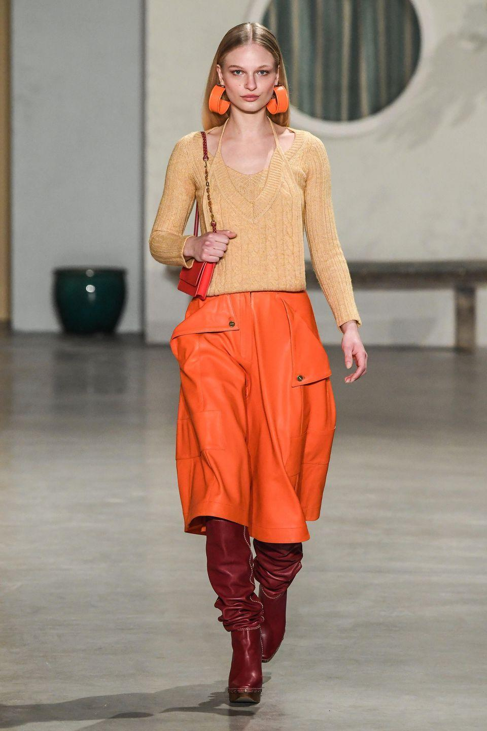 """<p>Simon Porte Jacquemus is that rare designer who truly understands the social media generation. He did create the giant hat and the tiny bags liked 'round the world, after all. For Fall 2019, he created his own little world, """"Place Jacquemus,"""" a colorful, Insta-worthy set inspired by a fictional town in the South of France-with colorful doors, distressed wooden benches, and clothes lines. The looks were South of France-worthy as well-with wide leg trousers under elongated vests and airy suiting in shades of light blue and cream. This is Fall though, after all, and the Jacquemus girl needs some knits, boots and coats and the designer was happy to comply with a layered, monochrome hot pink look, orange leather skirts and neutral sweaters. -<em>Kerry Pieri</em></p>"""
