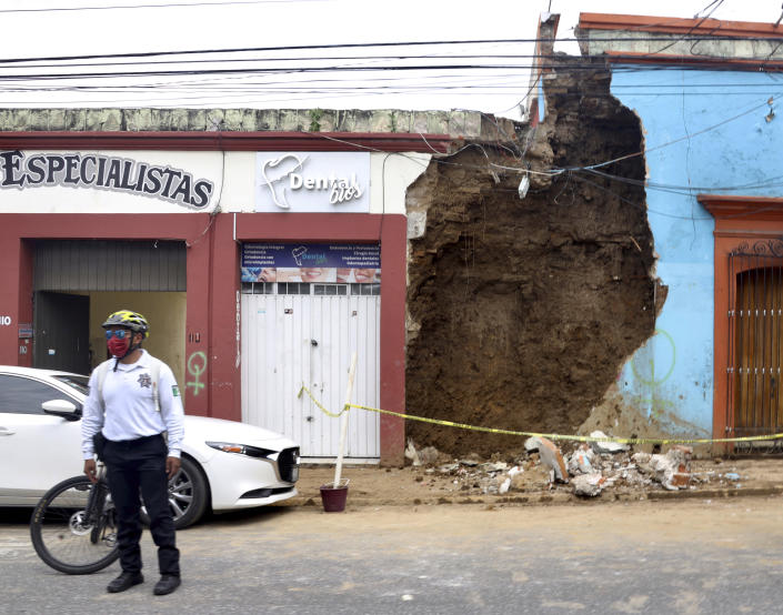 A policeman stands in front of a partially collapsed building after an earthquake in Oaxaca,, Mexico, Tuesday, June 23, 2020. The earthquake was centered near the resort of Huatulco, in the southern state of Oaxaca. (AP Photo/Luis Alberto Cruz Hernandez)