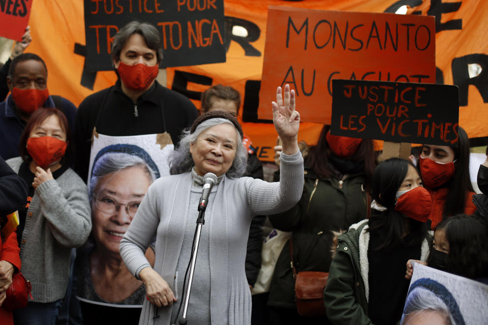 Tran To Nga, a 78-year-old former journalist, waves as she delivers a speech during a gathering in support of people exposed to Agent Orange during the Vietnam War, in Paris, Saturday Jan. 30, 2021. Activists gathered Saturday in Paris in support of people exposed to Agent Orange during the Vietnam War, after a French court examined a case opposing a French-Vietnamese woman to 14 companies that produced and sold the toxic chemical. (AP Photo/Thibault Camus)