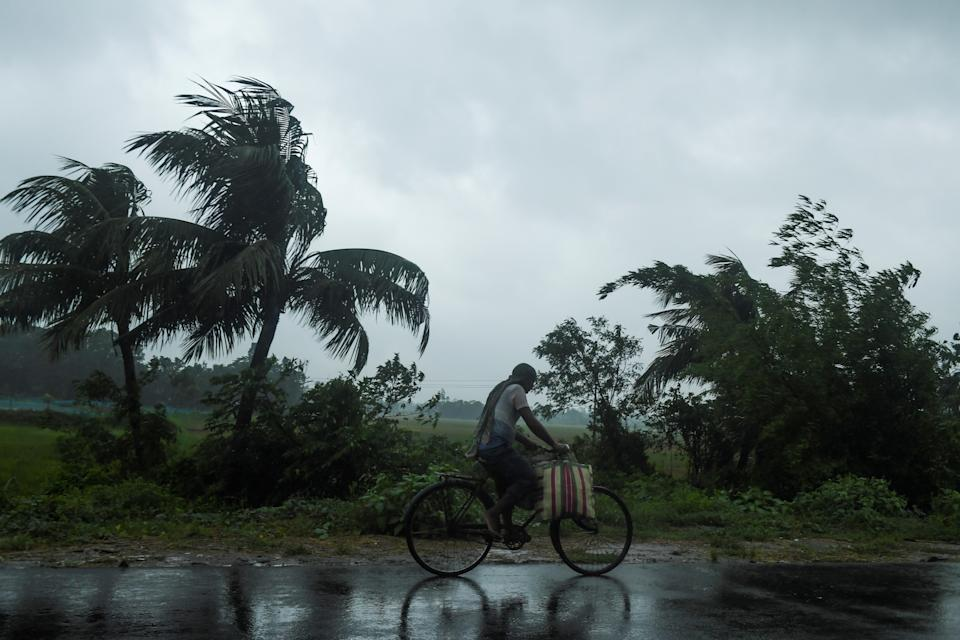 A man rides a bicycle under the rain ahead of the expected landfall of cyclone Amphan in Midnapore, West Bengal, on May 20, 2020. (Photo by Dibyangshu SARKAR / AFP)