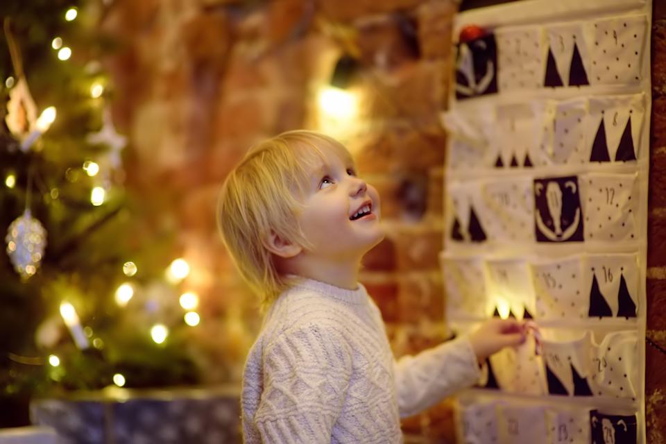 Happy little boy takes sweet from advent calendar on Christmas eve. Traditional christmas calendar for kids