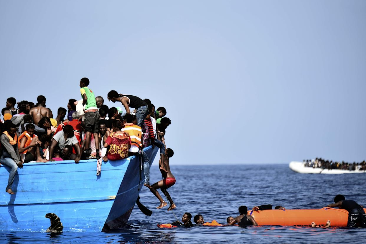 Migrants wait to be rescued by members of Proactiva Open Arms NGO as they drift in the Mediterranean Sea, some 12 nautical miles north of Libya, on October 4, 2016. At least 1,800 migrants were rescued off the Libyan coast, the Italian coastguard announced, adding that similar operations were underway around 15 other overloaded vessels. / AFP / ARIS MESSINIS (Photo credit should read ARIS MESSINIS/AFP/Getty Images)