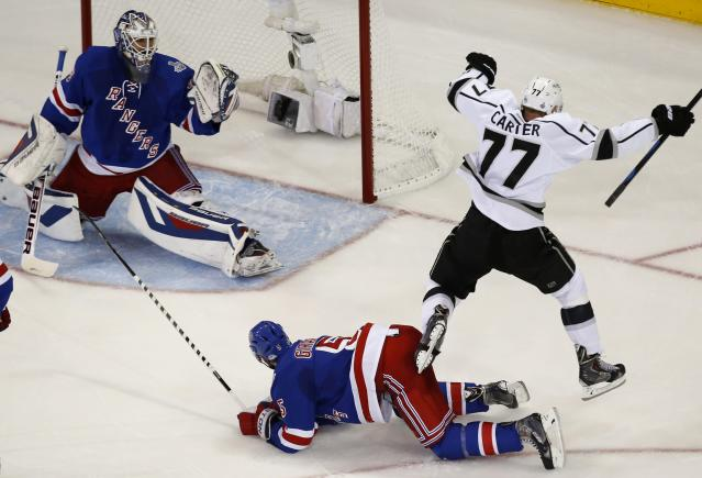 Los Angeles Kings Jeff Carter (R) celebrates his goal on New York Rangers' goalie Henrik Lundqvist (L) as he leaps over Rangers' Dan Girardi during the first period in Game 3 of their NHL Stanley Cup Finals hockey series in New York June 9, 2014. REUTERS/Shannon Stapleton (UNITED STATES - Tags: SPORT ICE HOCKEY)