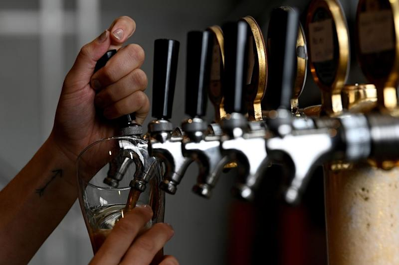 A bartender pours a glass of beer for a customer at a resturant in Sydney on May 15, 2020. - Sydney's bars and restaurants flung open their doors as a weeks-long lockdown eased Friday, but many remained quiet with only a few cautious patrons returning. (Photo by Saeed KHAN / AFP) (Photo by SAEED KHAN/AFP via Getty Images)