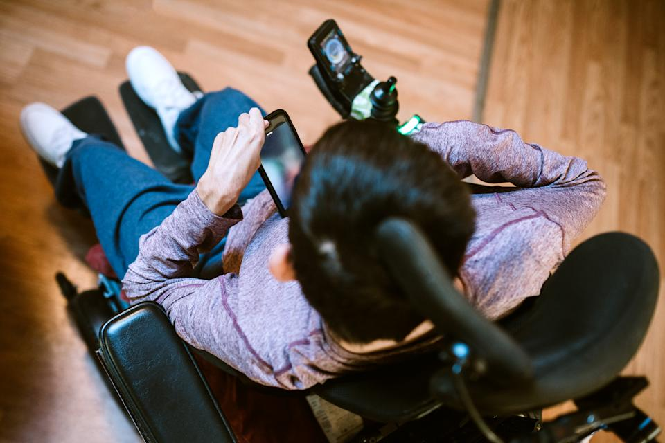 A cheerful young adult man with cerebral palsy researches texts someone on his smart phone, using voice recognition to aid in his communication.
