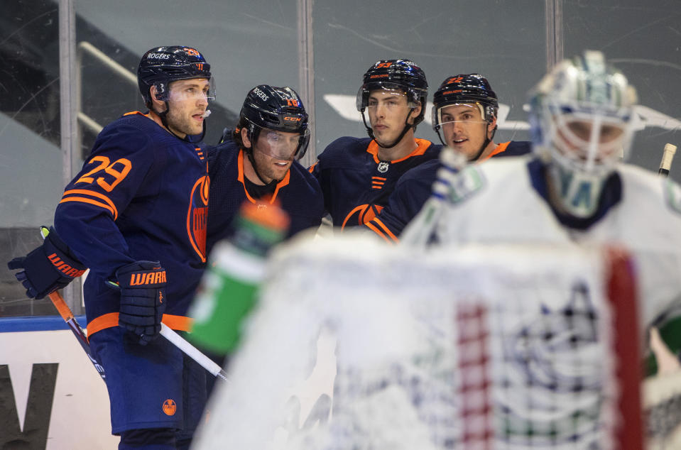Edmonton Oilers' Leon Draisaitl (29) celebrates his 500th NHL point with James Neal (18), Ryan Nugent-Hopkins (93) and Tyson Barrie (22), during the second period of an NHL hockey game against the Vancouver Canucks on Saturday, May 8, 2021, in Edmonton, Alberta. (Jason Franson/The Canadian Press via AP)