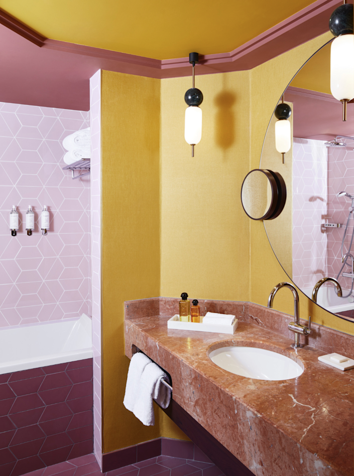 Pink asymmetrical ceramic tiles adorn the bathrooms and contrast with the yellow walls and ceilings.