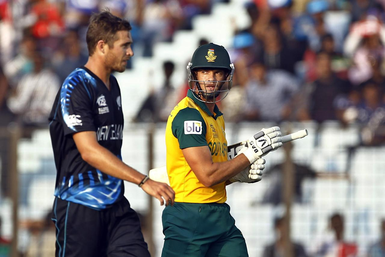 South Africa's Albie Morkel, right, walks back to the pavilion after his dismissal by New Zealand's Tim Southee, left, during their ICC Twenty20 Cricket World Cup match against New Zealand in Chittagong, Bangladesh, Monday, March 24, 2014. (AP Photo/A.M. Ahad)