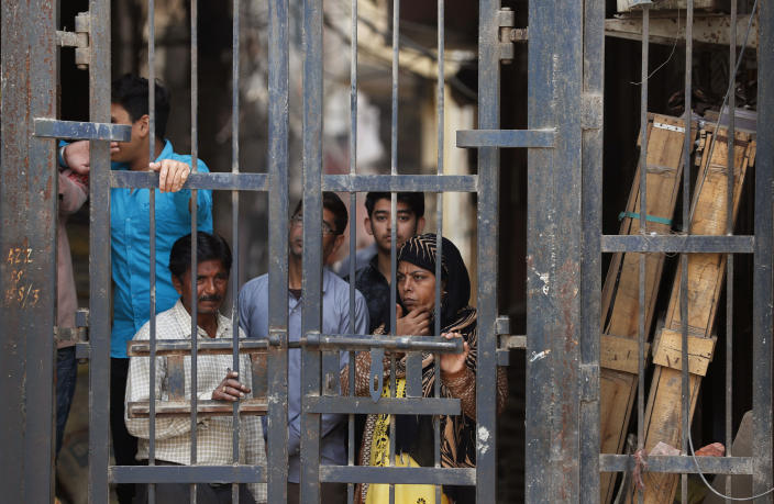 Residents look from behind a closed iron gate of their alley in Karaval Nagar following Tuesday's violence in New Delhi, India, Thursday, Feb. 27, 2020. India accused a U.S. government commission of politicizing communal violence in New Delhi that killed at least 30 people and injured more than 200 as President Donald Trump was visiting the country. The violent clashes between Hindu and Muslim mobs were the capital's worst communal riots in decades and saw shops, Muslim shrines and public vehicles go up in flames. (AP Photo/Rajesh Kumar Singh)