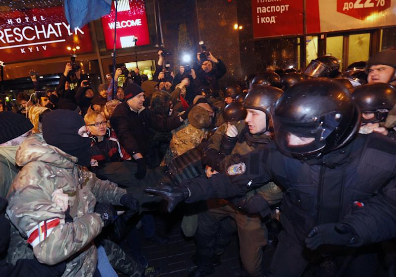 Far-right activists clash with riot police in front of an Alfa-Bank in central Kiev, Ukraine, Tuesday, March 14, 2017. Activists and supporters of Ukrainian nationalist groups are demanding the closure of all banks associated with Russia in Ukraine. (AP Photo/Sergei Chuzavkov)