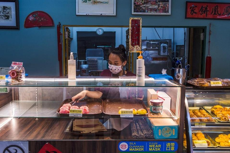 An employee is seen here arranging pastries at the Fung Wong Biscuits store along Jalan Hang Lekir. ― Picture by Shafwan Zaidon