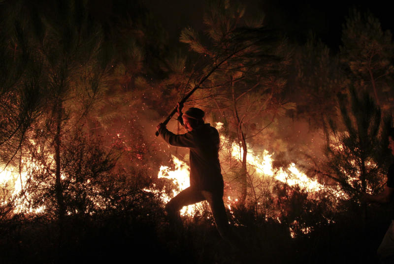 A man using a branch of a tree helps to extinguish a fire in Tondela, near Viseu, Portugal, Thursday night, Aug. 22, 2013. Portuguese authorities said one firefighter has died and six were injured as they battled a wildfire in Tondela. (AP Photo/Francisco Seco)