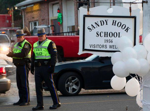 PHOTO: Police stand guard at the entrance after a mass shooting at the Sandy Hook School in Newtown, Conn., Dec. 15, 2012. (Don Emmert/AFP/Getty Images)