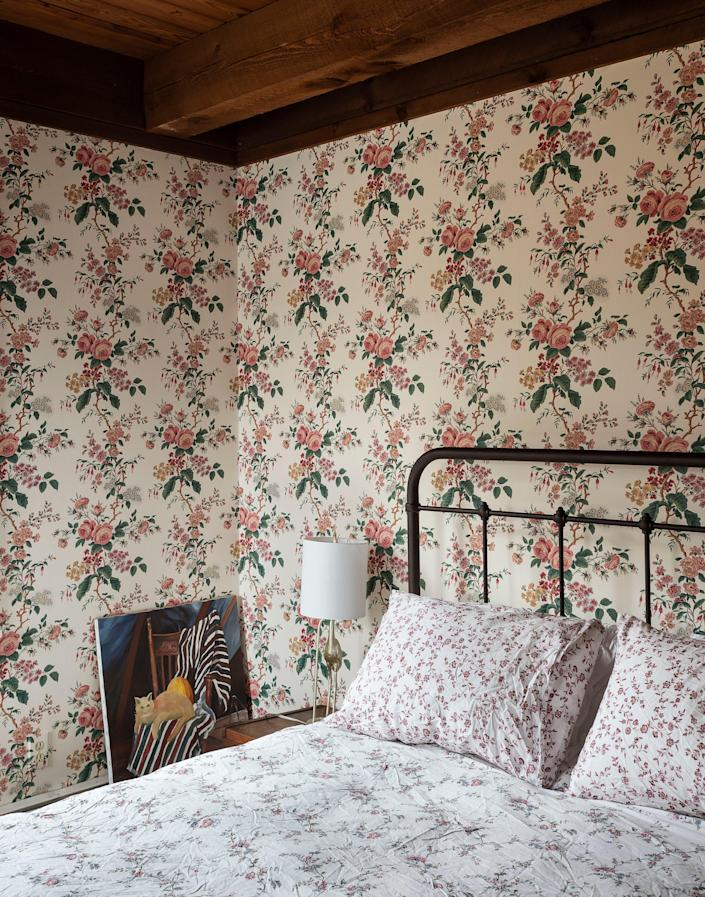 AFTER: Affectionately referred to as the cat room by the homeowners, this guest room includes wallpaper that was original to the previous owners. The new owners chose to keep it and emphasize it by bringing in floral bedding and hanging some cat paintings that were picked up in Hudson over time.