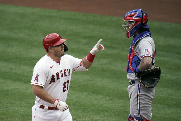 Los Angeles Angels' Mike Trout, left, celebrates his home run as Texas Rangers catcher Jonah Heim looks away during the first inning of a baseball game, Wednesday, April 21, 2021, in Anaheim, Calif. (AP Photo/Jae C. Hong)