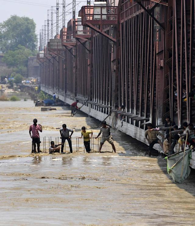 People watching the flooded river Yamuna after heavy monsoon rains from Iron bridge on June 19, 2013 in New Delhi, India. Several low-lying areas along the Yamuna were today flooded as the water level in the river was flowing two metres above the danger mark and inching towards touching the highest level of 207.49 m. (Photo By Sonu Mehta/Hindustan Times via Getty Images)