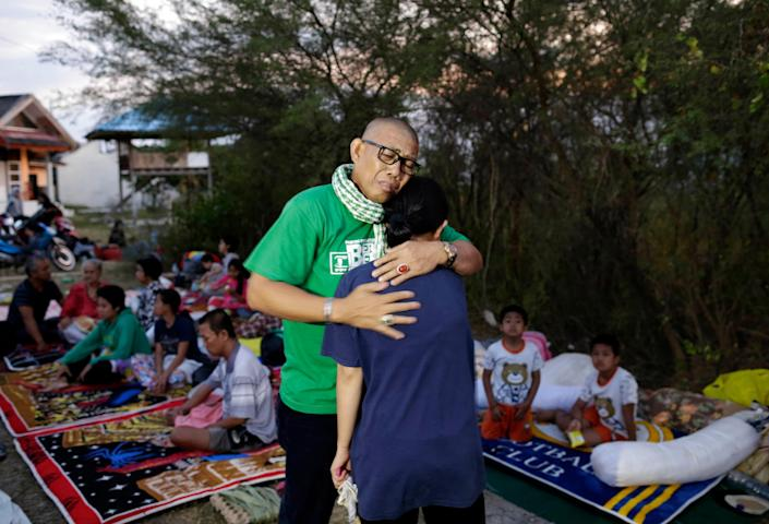 <p>An Indonesian man hugs his daughter who survived the earthquakes and tsunami as they reunite at an open air camp in Palu, Central Sulawesi, Indonesia, Sept. 29, 2018. (Photo: Mast Irham/EPA-EFE/REX/Shutterstock) </p>