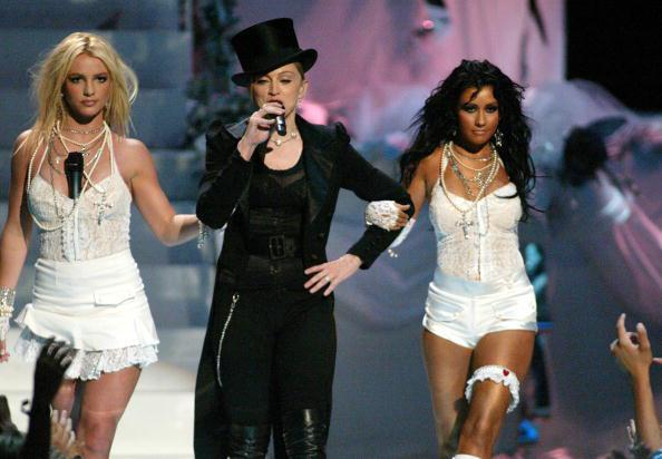 "<div class=""caption-credit""> Photo by: Getty Images</div><div class=""caption-title""></div><b>With Britney Spears and Christina Aguilera at the 2003 MTV VMAs</b> <br> The next generation recreateed Madonna's 1984 ""Like a Virgin"" routine dressed as brides. Soon their groom, Madonna herself, joined them on stage to sing ""Hollywood."""