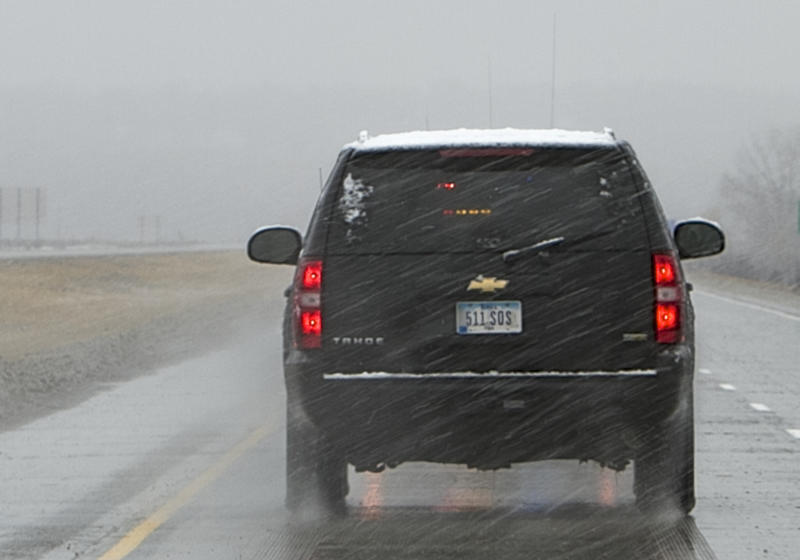 FILE - In this Nov. 2, 2011, file photo is a black SUV, with a license plate that is not on file in police databases, carrying Iowa Gov. Terry Branstad. State data shows that more than 3,200 license plates have been issued to local, state and federal agencies with a designation that allows them to avoid tickets from Iowa traffic cameras. (AP Photo/Nati Harnik, File)