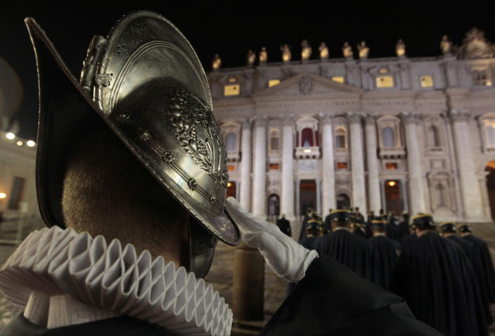 A Swiss guard salutes, in St. Peter's Square at the Vatican, Wednesday, March 13, 2013. The Catholic church has chosen a new pope. White smoke is billowing from the chimney of the Sistine Chapel, meaning 115 cardinals in a papal conclave have elected a new leader for the world's 1.2 billion Catholics. (AP Photo/Gregorio Borgia)
