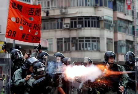 FILE PHOTO: Police officers fire tear gas as anti-extradition bill protesters demonstrate in Sham Shui Po neighbourhood in Hong Kong
