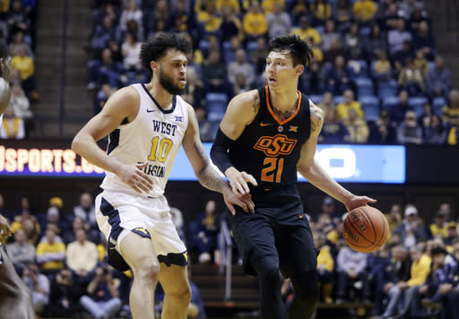 Oklahoma State guard Lindy Waters III (21) drives up court against West Virginia guard Jermaine Haley (10) during the first half of an NCAA college basketball game Saturday, Jan. 12, 2019, in Morgantown, W.Va. (AP Photo/Raymond Thompson)