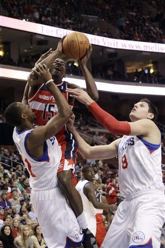 Washington Wizards' Jordan Crawford (15) goes up for a shot as Philadelphia 76ers' Thaddeus Young (21) and Nikola Vucevic (8), of Switzerland, defend in the first half of an NBA basketball game, Friday, Jan. 13, 2012, in Philadelphia. (AP Photo/Matt Slocum)