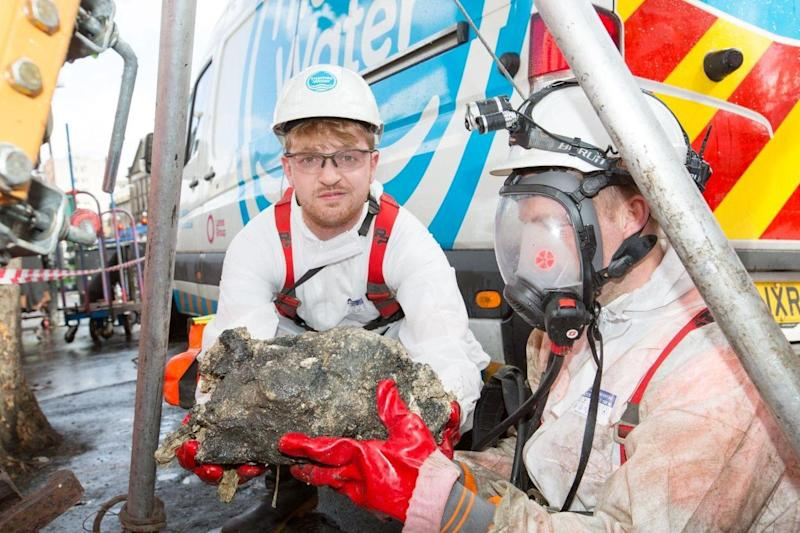 Sam Fishwick with part of the fatberg in a sewer in Whitechapel, east London: Matt Writtle