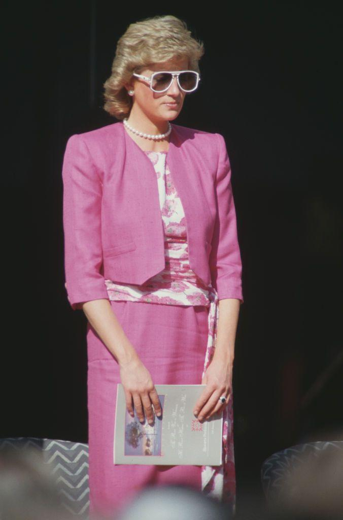 """<p>Diana had <a href=""""https://www.townandcountrymag.com/society/tradition/g37374670/royal-family-pink-fashion-photos/"""" rel=""""nofollow noopener"""" target=""""_blank"""" data-ylk=""""slk:a pink moment"""" class=""""link rapid-noclick-resp"""">a pink moment</a> during a trip to Sydney, Australia in January 1988. The Princess chose a cropped pink blazer, a matching skirt, and a bold pair of sunglasses for this outing.<br></p>"""