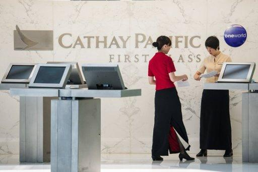 Cathay Pacific employees are seen at a first class booth at the airport in Hong Kong on August 7, 2012. Cathay Pacific Airways posted a first-half net loss of US$121 million, citing higher fuel prices, strong competition and economic instability in Europe