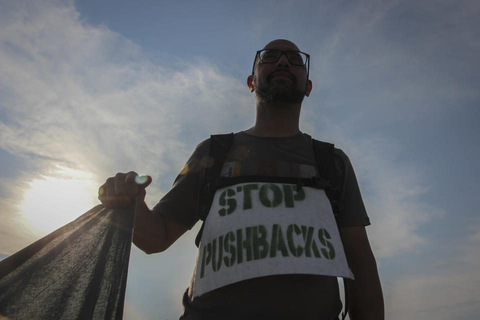 A man holds a banner during a protest against the violent pushbacks of migrants, allegedly conducted by Croatian police, near the border crossing between Croatia and Bosnia Herzegovina in Maljevac, Croatia, Saturday, June 19, 2021. More than one hundred members of human rights NGO's, mostly from Italy, but also from Germany, Austria, Spain and Slovenia blocked the border traffic for about two hours protesting demanding a stop of all deportation of migrants, and cancellation of EU's Frontex operations at borders, preventing migrants from traveling. (AP Photo/Edo Zulic)