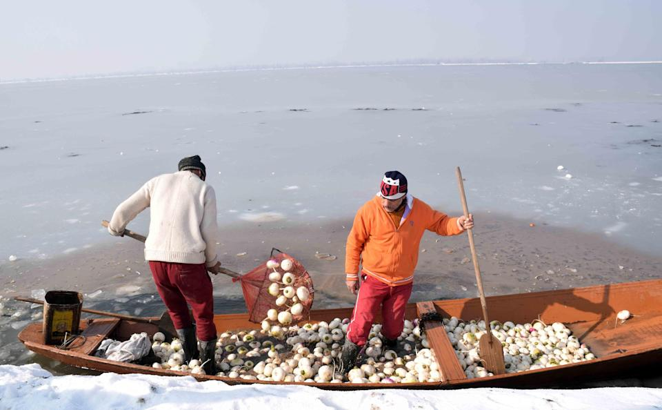 A vegetable vendor breaks the sheet of ice covering the Dal Lake in order to row his boat.