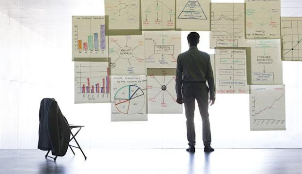 Businessman looking at graphs and charts on glass wall in office