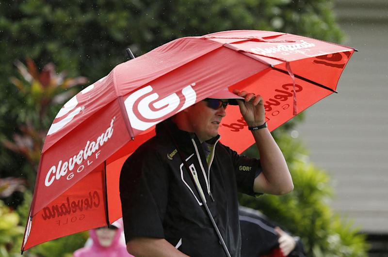 Charlie Beljan holds an umbrella as he waits his turn to tee off in the first round at the Tournament of Champions golf tournament on Friday, Jan. 4, 2013, in Kapalua, Hawaii. (AP Photo/Elaine Thompson)