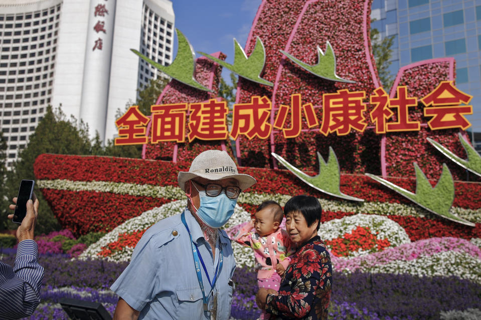 """A man wearing a face mask to help curb the spread of the coronavirus walks by a woman with a child posing for a souvenir photo near a floral decoration baring the words """"Fully built a well-off society"""" for celebrating the up-coming National Day in Beijing, Wednesday, Sept. 30, 2020. Even though the spread of COVID-19 has been all but eradicated in China, the pandemic is still surging across the globe with ever rising death toll. (AP Photo/Andy Wong)"""