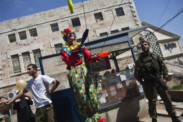 An Israeli soldier (R) stands guard as he watches a man dressed in a clown costume juggle during a parade for the Jewish holiday of Purim in the West Bank city of Hebron March 8, 2012. Purim is a celebration of the Jews' salvation from genocide in ancient Persia, as recounted in the Book of Esther.