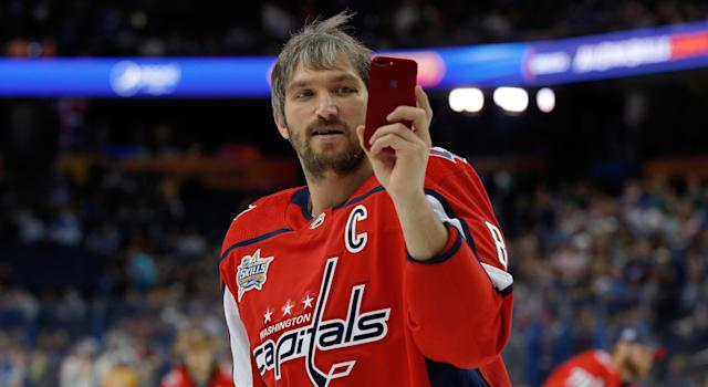 Even Alexander Ovechkin is checking out the Yahoo Fantasy app on his phone, probably. (Photo by Mike Carlson/Getty Images)
