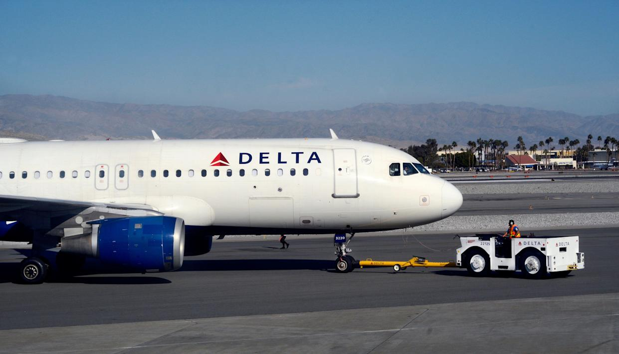A Delta Air Lines ground crew member pushes a passenger aircraft from the gate at Palm Springs International Airport in Palm Springs, California. (Photo credit: Robert Alexander/Getty Images)