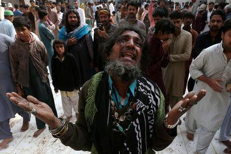 FILE PHOTO -  A man mourns the death of a relative who was killed in a suicide blast at the tomb of Sufi saint Syed Usman Marwandi, also known as the Lal Shahbaz Qalandar shrine, on Thursday evening in Sehwan Sharif