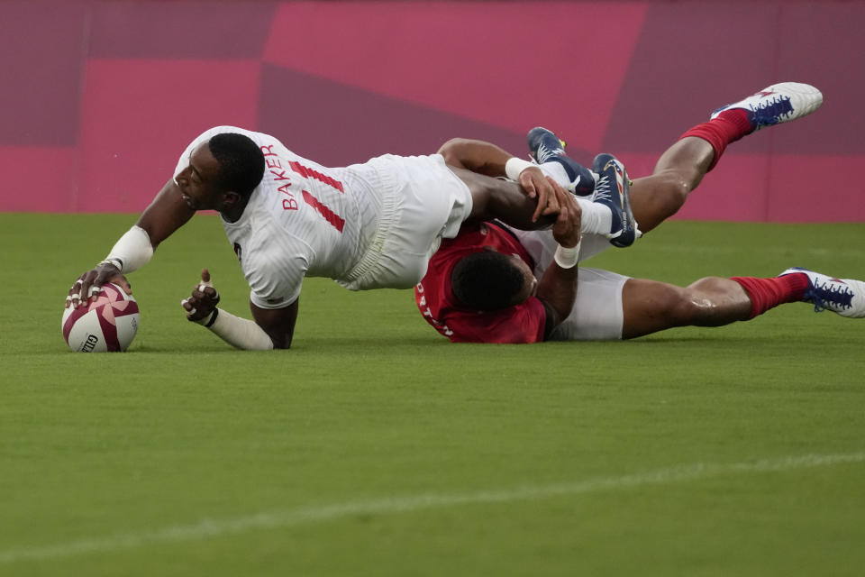 Perry Baker of the United States scores a try, despite a tackle by Britain's Dan Norton, in their men's rugby sevens quarterfinal match at the 2020 Summer Olympics, Tuesday, July 27, 2021 in Tokyo, Japan. (AP Photo/Shuji Kajiyama)