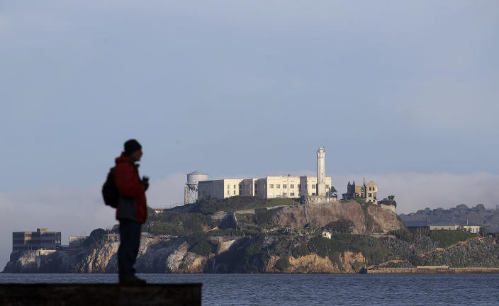 A man stands on a pier with Alcatraz Island in the background in San Francisco, Dec. 22, 2018. The company that provides ferry services to Alcatraz Island kept its daytime tours but canceled its behind-the-scenes and night tours on Saturday due to the government shutdown. (Photo: Jeff Chiu/AP)