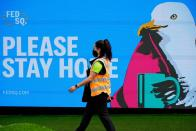 An essential worker walks past a 'Please Stay Home' sign on the first day of a five-day COVID-19 lockdown in Melbourne