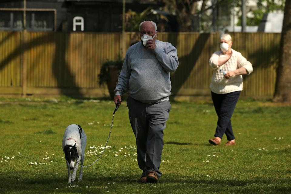 """A man walks his dog as people exercise wearing protective face masks in Archbishop's Park, behind St Thomas' Hospital in central London on April 9, 2020, where Britain's prime minister is in intensive care as he fights the novel coronavirus COVID-19. - British Prime Minister Boris Johnson on Thursday began a fourth day in intensive care """"improving"""" in his battle with coronavirus, as his government prepared to extend a nationwide lockdown introduced last month. (Photo by Isabel Infantes / AFP) (Photo by ISABEL INFANTES/AFP via Getty Images)"""
