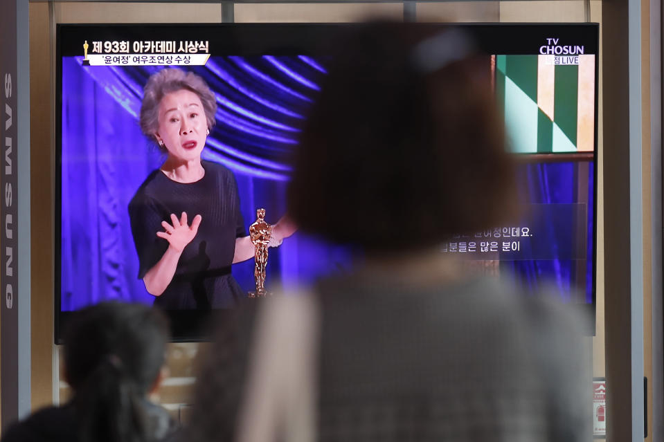 """People watch a live broadcast on TV showing South Korean actress Yuh-Jung Youn receiving the Oscar for best supporting actress for her performance in """"Minari,"""" at Seoul Railway Station in Seoul, South Korea, Monday, April 26, 2021. (AP Photo/Lee Jin-man)"""