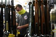 A customer looks at guns at Coliseum Gun Traders Ltd. in Uniondale, New York