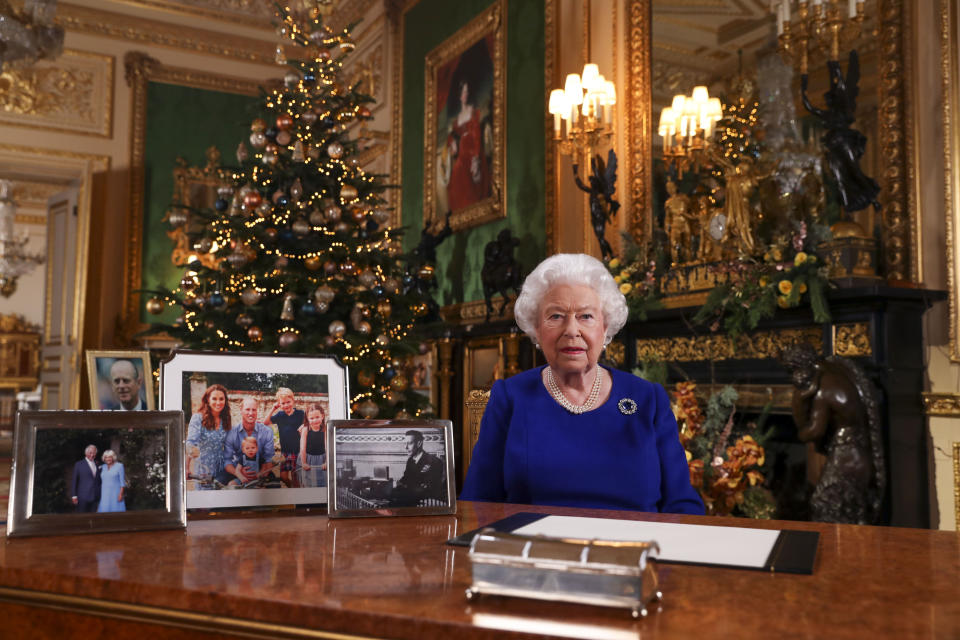 The Queen recording her annual Christmas broadcast in Windsor Castle surrounded by pictures of her family. (PA)